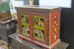 An Indian painted hardwood cabinet, the top with floral and leaf spray, with gilded border, above