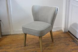 A modern ash framed bedroom chair with curved upholstered back and seat in grey linen fabric, raised