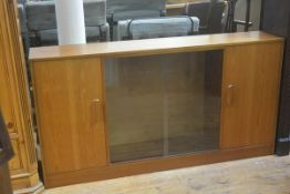 A 1970s teak G Plan bookcase with twin sliding centre panel doors, flanked by panel doors, with