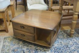 An Ercol elm coffee table, the shaped squared top with rounded angles and open sides, fitted two