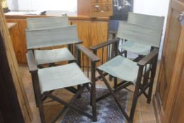 A set of four stained beech 1920s director's style chairs with green canvas back and seats, raised