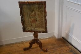 A Victorian rosewood snap top firescreen with relief carved border and glazed Berlin woolwork