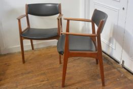 A pair of 1960s teak vinyl upholstered curved panel back and seat open armchairs (one seat