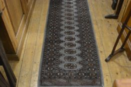 A modern Bokhara runner, the central panel with fifteen medallions enclosed within a stylised floral