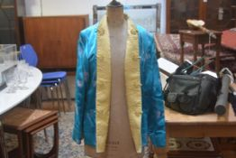 A Chinese gold and turquoise silk embroidered reversible short jacket with slash pockets to front (