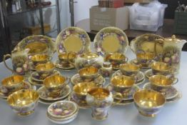 An Aynsley china gilded fifty two piece tea and coffee service with transfer printed fruit, complete
