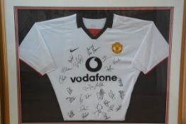 A Manchester United Alex Ferguson signed and team signed white Vodafone shirt in gilt glazed