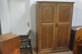 An oak two door cupboard, the moulded cornice above a pair of fielded panel doors, enclosing a