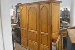 A French pine triple panel door armoire with moulded cornice, fitted three drawers, raised on plinth
