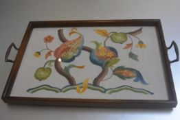 A 1920s oak glazed twin handled tea tray with hand embroidered running stitch pomegranate tree