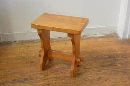 A pine stool, the rectangular top raised on shaped end supports united by stretcher (h.45mc x 41cm x