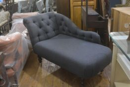 A neat modern chaise longue with upholstered button back and scroll arm, in grey felted wool, raised