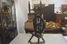 A 19thc stained oak spinning wheel complete with foot pedal on tripod turned tapered support (some