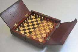 An Edwardian mahogany folding chessboard complete with carved bone chessmen (two missing) (h.6cm x