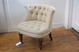 An early 19thc style low chair with button back, in cream linen, with studded detail, on turned