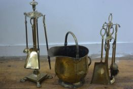 A four piece brass companion set on circular urn finial stand and paw feet, complete with brush etc.