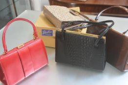 A lady's brown patent leather bag, a faux crocodile black leather two handled bag, a pink double