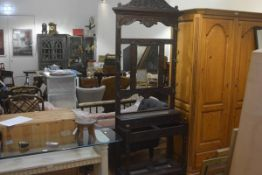 A Victorian carved oak mirror back hallstand, the pedimented relief carved cresting rail above a