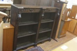 A Victorian oak upright open bookcase, the shaped top with relief carved urn and radiating frieze
