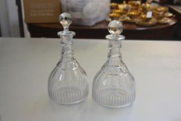 A pair of 19thc Irish style lead crystal thumb cut triple ring neck decanters, with later faceted