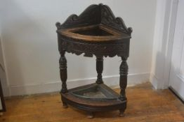 A late 19thc oak carved corner hall stick stand with relief carved shaped panel back and frieze,