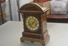 An Edwardian walnut mantle clock with arched top above an enamelled dial with twin key apertures and