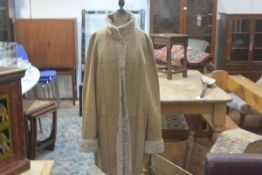 An astrakan blonde tan hide three quarter length reversible coat with slit pockets and button