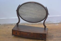 A 19thc mahogany swing mirror, the oval mirror raised on scroll end supports and bow fronted base,