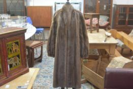 A lady's wild mink fur coat with leather loop belt, with slash pockets and satin lining (l. 110cm)