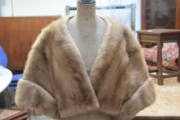 A lady's ranch mink opera shrug, with satin lining and single pocket (38cm x 43cm)