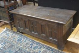 A reproduction oak coffer, the rectangular hinged top enclosing a plain interior above three arcaded