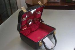 A lady's Cheney black patent vinyl vanity case with pink lined interior, complete with original