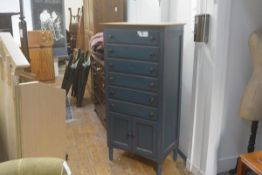 A distressed blue painted pine tallboy chest, fitted six long drawers above a pair of panel doors,
