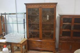 A reproduction mahogany cabinet on stand, the moulded cornice above a pair of glazed astragal