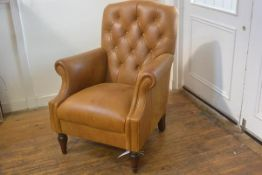 A modern Victorian style tan hide button back club style chair with scroll arms, raised on turned