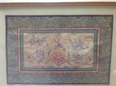A Chinese silk panel, worked in polychrome threads with pheasants and blossoms, within a geometric
