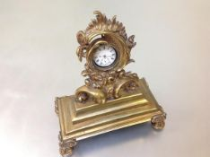 A 19th century gilt bronze watch stand, the aperture within a frame cast with Rococo style shells,