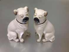 A pair of late 19th century Staffordshire large models of seated pugs, cream glazed and with black