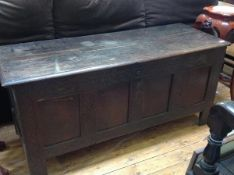 A late 17th/early 18th century oak four-panel coffer, the plain rectangular cover with moulded edge,