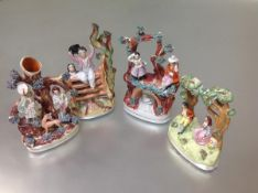 A group of Staffordshire figure groups comprising: a dancer and musician over a bridge; a spill vase