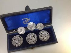 A cased set of three Edwardian silver lady's buttons, Birmingham 1901, each circular, pierced with
