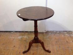 A George III mahogany tilt-top mahogany tripod table, the circular top on a ring-turned tapering