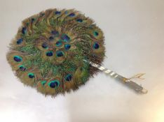 A peacock feather fan, c. 1900, circular, with bound handle. Length 37cm