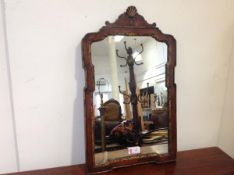 A George II parcel-gilt walnut wall mirror, the shaped moulded frame enclosing a gilt slip and