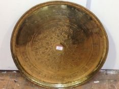 A Middle Eastern brass tray, circular, the well with central roundel of star design enclosing