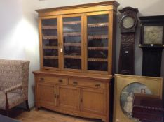 A golden oak bookcase cabinet c. 1900, the upper section with moulded cornice above three glazed