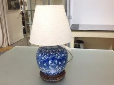 A Chinese style blue and white porcelain table lamp, decorated with flowering branches, on an