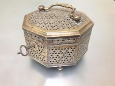 An Indo-Persian brass casket, of octagonal form, pierced throughout and with swing handle and key,