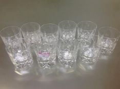 A set of ten cut-glass whisky tumblers, each cylindrical with thumb cut bowl on a star-cut foot.