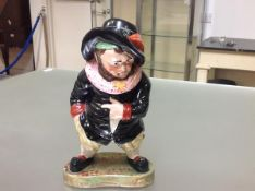 A 19th century Mansion House style pottery tobacco jar and cover, modelled as a dwarf in feathered